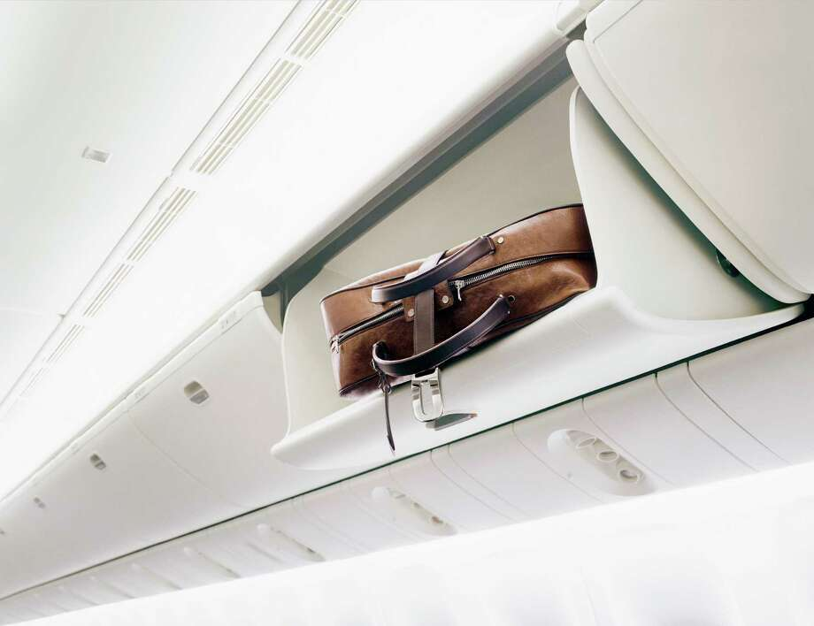 5. Bin jumping. Why is there a bag in this bin but no passenger in that row? Because someone 10 rows back claimed the space for his stuff. Photo: Benedict Redgrove, Getty Images / (c) Benedict Redgrove