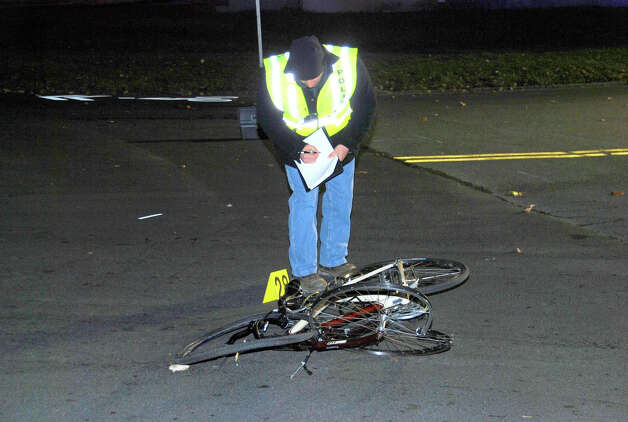 An investigator examines the bicycle Paul Merges of Albany was riding near the intersection of Central Avenue and Manning Boulevard when he was struck and killed by a Chevrolet pickup truck authorities say Pablo Cruz was driving in a high-speed chase with Albany County Sheriff's deputies early Saturday, Nov. 24, 2012. (Thomas Heffernan Sr./Special to the Times Union) Photo: Picasa