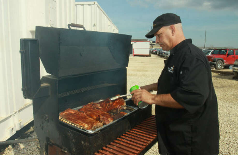Chef Mark Semkiw of Premier Offshore Catering, prepares barbecue ribs and chicken for workers assembling Shell's Olympus platform at the Lonestar Energy Fabrication yard in Baytown, Texas.