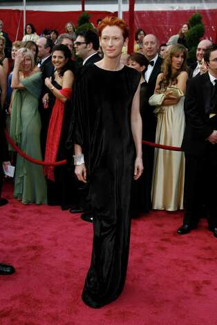 "Tilda Swinton, 2008: This dress is not well-loved but the look is iconic and all Tilda. The black washed silk Lanvin is a Frankenstein of a frock: all baggy and long-sleeved on one side and straight up and down sleeveless on the other side. But Tilda (somehow referring to her as ""Swinton"" seems too formal) wore it proudly with her red pompadour as she collected her best supporting actress Oscar for ""Michael Clayton."" Tilda will be forever remembered for the ""Hefty bag"" dress and for one unanswered question torturing fashionistas the world over: why didn't she at least wear the cuff on the sleeveless arm? (Daniel A. Anderson/Orange County Register/MCT) Photo: DANIEL A. ANDERSON, McClatchy-Tribune News Service / Orange County Register"