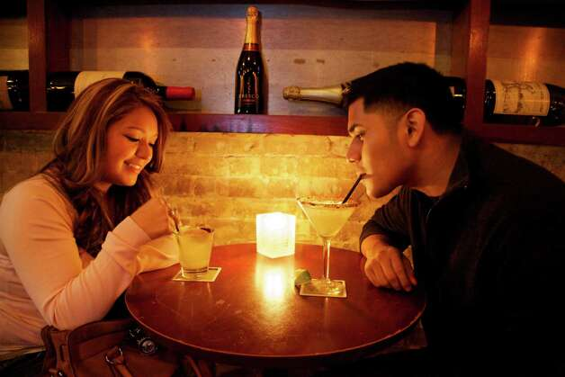 Stephanie Rodriguez and Luis Pimentel sip drinks.