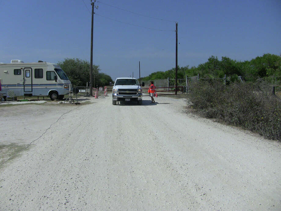A Gate Guard Services attendant, who lives in the RV at left, speaks with a visitor to a site outside Portland, in San Patricio County near Corpus Christi.