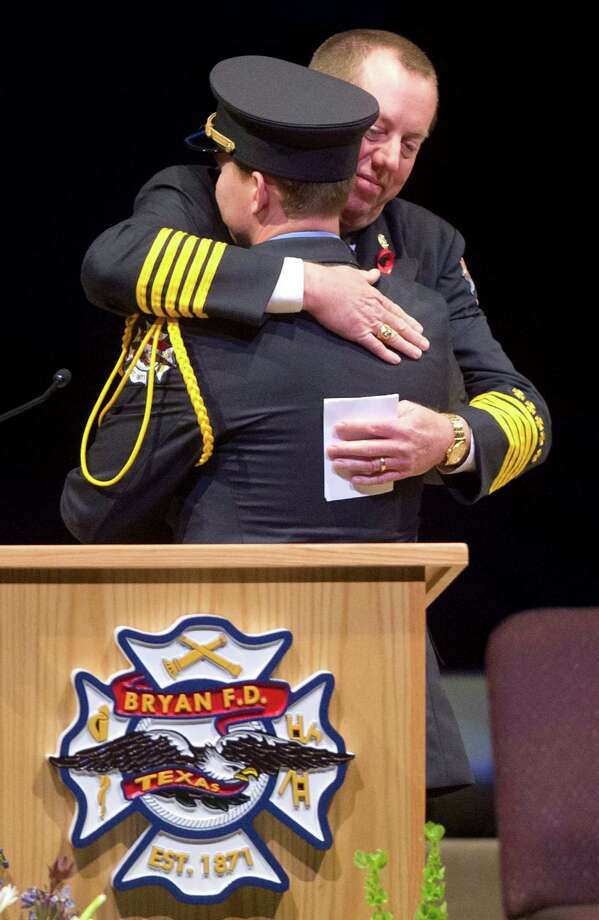 Bryan Fire Chief Randy McGregor (R) embraces Bryan firefighter Lt. DJ Capener at the memorial service for Bryan firefighters Eric Wallace and Gregory Pickard at Central Baptist Church in Bryan, Texas, Wednesday, Feb. 20, 2013. Photo: Stuart Villanueva, Associated Press / The College Station Eagle