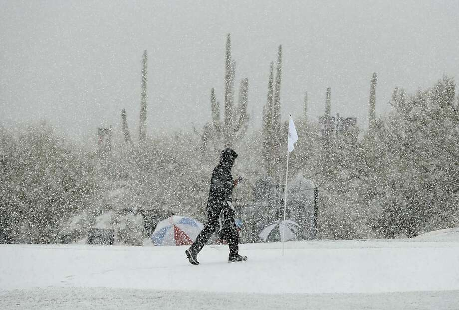 A volunteer walks along the practice green as snow falls on the Match Play Championship in Arizona. Photo: Ross Franklin, Associated Press