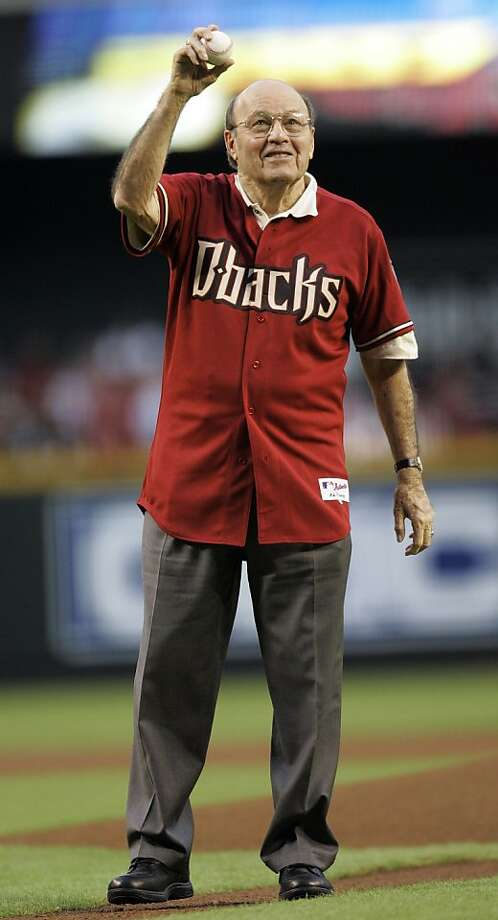 FILE - In this Oct. 11, 2007, file photo, Hall of Fame broadcaster Joe Garagiola throws out the ceremonial first pitch before Game 1 of the National League Championship baseball series between the Arizona Diamondbacks and Colorado Rockies in Phoenix. Garagiola, whose career transcended sports with his sharp sense of humor and limitless list of stories to tell, announced during a news conference on Wednesday, Feb. 20, 2013, that he is calling it quits as part-time television game analyst for the Diamondbacks. (AP Photo/Morry Gash, File) Photo: Morry Gash, Associated Press