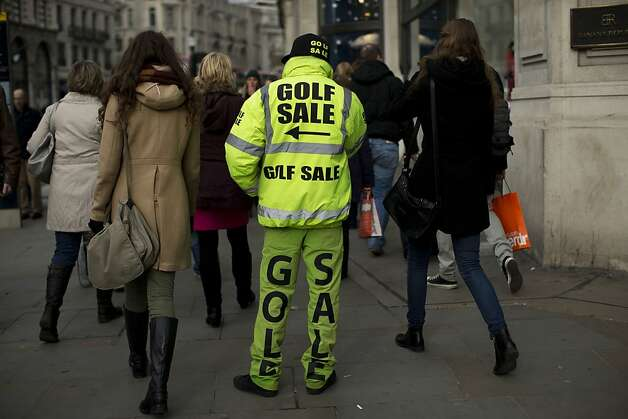 A man advertises a golf sale on Regent Street in London, Wednesday, Feb. 20, 2013. (AP Photo/Matt Dunham) Photo: Matt Dunham, Associated Press