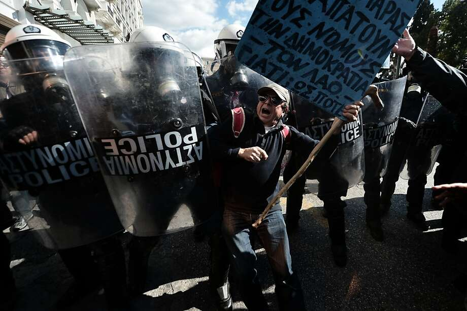 A demonstrator tries to pass a riot police cordon during a 24-hour general strike in Athens on February 20, 2013.  Greece was hit by a new strike on February 20 called by leading unions against unrelenting austerity in the recession-weary nation ahead of an audit by international creditors, disrupting flights, ferries and hospital services. The strike -- the first general work stoppage in debt-crippled Greece this year -- has forced airport authorities to scrap or reschedule dozens of flights while hospitals were operating on reduced staffing. AFP PHOTO / ARIS MESSINISARIS MESSINIS/AFP/Getty Images Photo: Aris Messinis, AFP/Getty Images