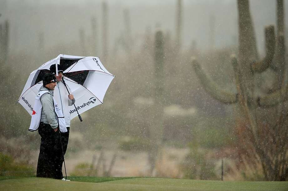 MARANA, AZ - FEBRUARY 20:  Marcus Fraser of Australia stands under an umbrella with his caddie as snow and rain fall during the first round of the World Golf Championships - Accenture Match Play at the Golf Club at Dove Mountain on February 20, 2013 in Marana, Arizona.  (Photo by Stuart Franklin/Getty Images)  Photo: Stuart Franklin, Getty Images