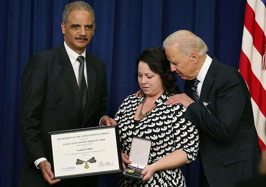 WASHINGTON, DC - FEBRUARY 20: U.S. Vice President Joseph Biden (R) and Attorney General Eric Holder (L) give the Medal of Valor to Angela Miller, widow of fallen Pennsylvania State Trooper Joshua D. Miller, during an event in Eisenhower Executive Office Building, February 20, 2013 in Washington, DC. Vice President Biden presented the award to public safety officers who have exhibited exceptional courage, regardless of personal safety, in the attempt to save or protect others from harm.  (Photo by Mark Wilson/Getty Images) *** BESTPIX *** Photo: Mark Wilson, Getty Images