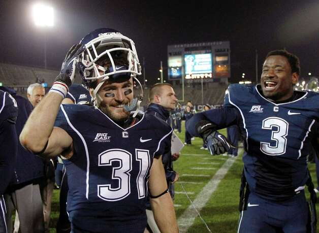 Connecticut wide receiver Nick Williams (31) smiles as he celebrates with teammate linebacker Sio Moore (3) after the team's 24-17 win in an NCAA college football game against Pittsburgh in East Hartford, Conn., Friday, Nov. 9, 2012. Williams returned a punt 80 yards for a touchdown. (AP Photo/Charles Krupa) Photo: Charles Krupa, Associated Press / AP