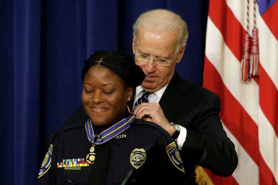 Vice President Joe Biden presents the Medal of Valor to Officer Reeshemah Taylor of the Osceola County Corrections Department in Florida., Wednesday, Feb. 20, 2013, during a ceremony in the Eisenhower Executive Office Building on the White House complex in Washington. The medal is the highest national award for valor by a public safety officer. The medal is awarded to public safety officers who have exhibited exceptional courage, regardless of personal safety, in the attempt to save or protect human life.  (AP Photo/Charles Dharapak) Photo: Charles Dharapak