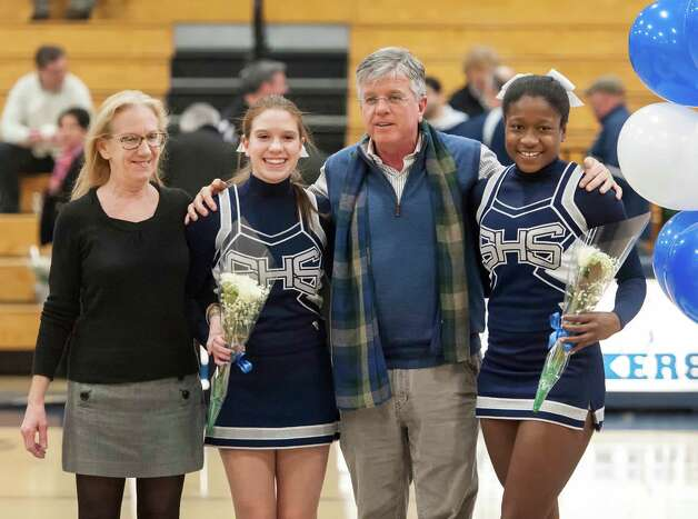 Staples cheerleaders, Maddy Mann and Jasmone Henry, take part in the senior night ceremony before the Staples high school boys basketball game against Bassick high school played at Staples high school, Westport, CT Wednesday February 20th, 2013. With the two are Maddy's parents. Photo: Mark Conrad / Connecticut Post Freelance