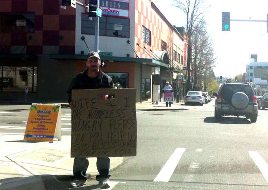 "Technically, the homeless man holding the sign is violating the law, though he wouldn't be if he were on the sidewalk, police said. Because he's in the street, that might be considered pedestrian interference, though chances are police would likely just ask him to get on the sidewalk if there was a problem. A person is guilty of pedestrian interference – a misdemeanor - if he or she obstructs pedestrian or vehicular traffic by aggressively begging. The other guy carrying the advertising sign in the background is fine in the picture, Detective Jeff Kappel said. So which sign in the picture is in violation of a Seattle law? The standalone sign on the sidewalk. The Seattle Department of Transportation ""allows each business to have one A-frame sign on the sidewalk, but that sign must be positioned near the business' entrance and not create a hazard for sidewalk users,"" department spokesman Rick Sheridan said. SDOT wars businesses in violation, though they could also give a $250 fine for lack of compliance. (Casey McNerthney/seattlepi.com file)"