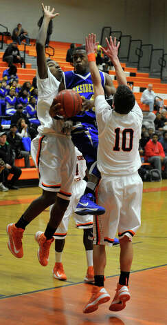 Harding's Reggie Stewart attempts to shoot as he is surrounded by Stamford's Errald Jordine, left, and Lucas Laria during their game at Stamford High School on Wednesday, Feb. 20, 2013. Harding won, 63-62. Photo: Jason Rearick / The Advocate