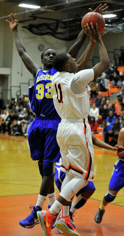 Stamford's Jelani Tonge shoots into the hands of Harding's Dennis Hinds during their game at Stamford High School on Wednesday, Feb. 20, 2013. Harding won, 63-62. Photo: Jason Rearick / The Advocate