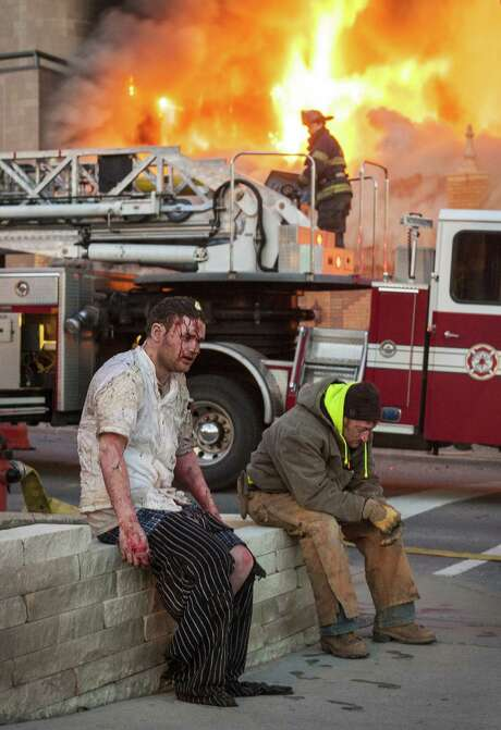Dazed victims and workers are shown at the scene of Tuesday's explosion and four-alarm fire at a restaurant in Kansas City, Mo. Surveillance video from a nearby travel agency shows a fireball erupting from the restaurant's roof, showering the street with debris and throwing up a cloud of dust and smoke. The blast could be felt for a mile and shattered glass in neighboring buildings. Photo: Bob Greenspan / Kansas City Star