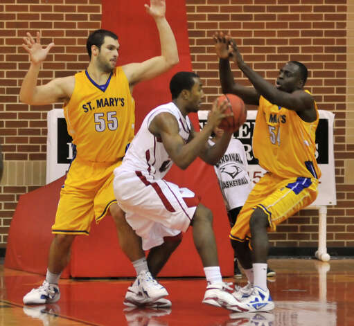 UIW's Chris Johnson is surrounded by St. Mary's players Kevin Kotzur (55) and Moses Sundufu during first half action on Dec. 29, 2011. Photo: Robin Jerstad, For The Express-News / SAN ANTONIO EXPRESS-NEWS