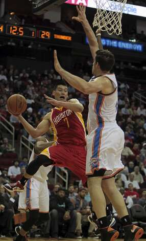 Rockets point guard Jeremy Lin looks to pass while in midair.