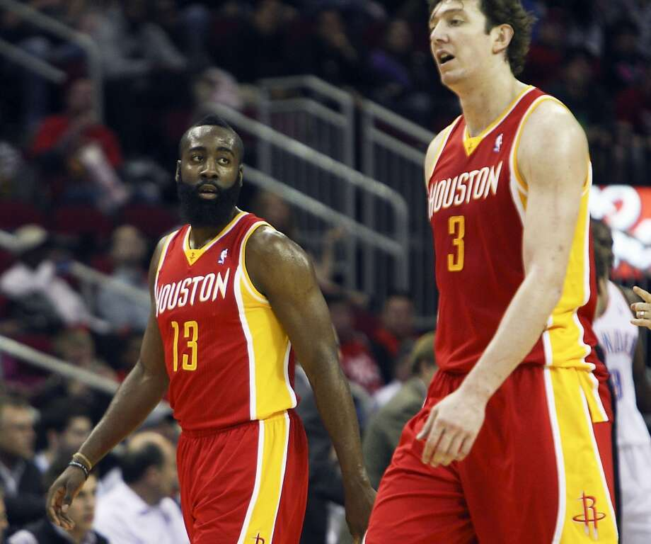 Omer Asik and James Harden of the Rockets walk off the court while playing the Thunder.