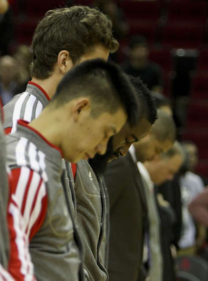 Rockets players pause during pregame ceremonies.