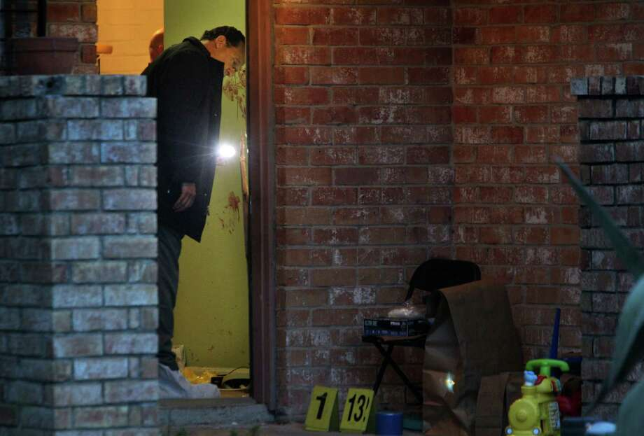 A Harris County sheriff's investigator inspects the scene of a fatal Tuesday night stabbing. Photo: Mayra Beltran, Staff / © 2013 Houston Chronicle