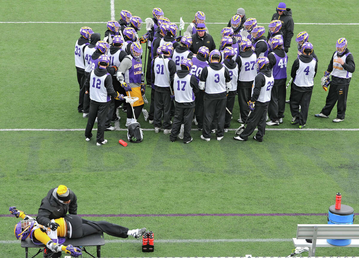 UAlbany lacrosse head coach Scott Marr talks to his team while athletic trainer Anthony Benyarko stretches Dwayne Stewart during a practice on Wednesday Feb. 20, 2013 in Albany, N.Y. (Lori Van Buren / Times Union)