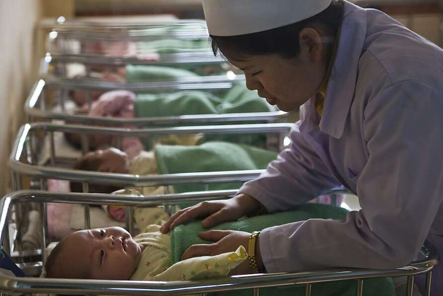 A North Korean nurse comforts a baby at a nursery inside Pyongyang Maternity Hospital in Pyongyang,