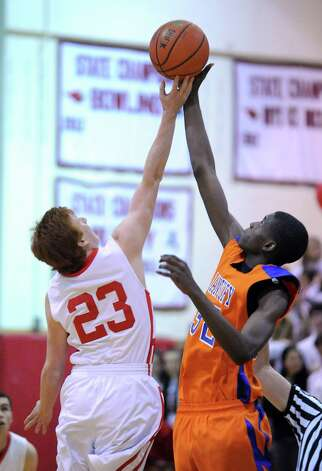 At left, Jake Tennenbaum # 23 of Greenwich jumps center against Jalen McCallum # 32 of Danbury during the boys high school basketball game between Greenwich High School and Danbury High School at Greenwich, Wednesday, Feb. 20, 2013. Photo: Bob Luckey / Greenwich Time