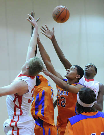 Danbury's Donovan Trimandillis # 12, at center, goes for a rebound against Leonel Hyatt of Greenwich, right, and Hyatt's teammate, Alex Wolf, left, during the boys high school basketball game between Greenwich High School and Danbury High School at Greenwich, Wednesday, Feb. 20, 2013. Photo: Bob Luckey / Greenwich Time