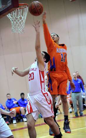 At left, Jimmy Djema # 20 of Greenwich, just gets his layup past Danbury's Marquise Marrero # 11 who was attempting a block during the boys high school basketball game between Greenwich High School and Danbury High School at Greenwich, Wednesday, Feb. 20, 2013. Photo: Bob Luckey / Greenwich Time