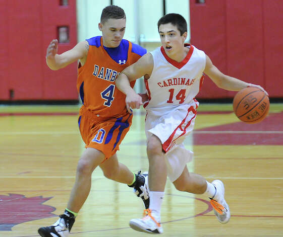 At left, Corey Chaffee # 4 of Danbury defends against a driving Thomas Baietto # 14 of Greenwich during the boys high school basketball game between Greenwich High School and Danbury High School at Greenwich, Wednesday, Feb. 20, 2013. Photo: Bob Luckey / Greenwich Time