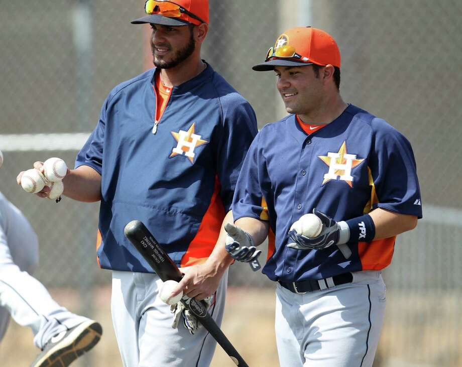 Astros Fernando Martinez (left) and Jose Altuve chat while returning balls to a bucket during a workout Wednesday in Kissimmee, Fla. Photo: Karen Warren / Houston Chronicle