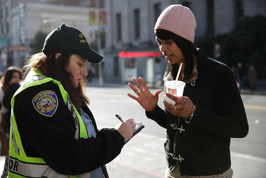 Michelle Sweetman (l to r), SFMTA transit fare inspector, writes a ticket for Melissa Washington of San Francisco for not having valid proof of payment upon request at a Muni bus stop on Wednesday, February 20, 2013 in San Francisco, Calif. Photo: Lea Suzuki, The Chronicle