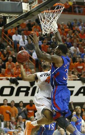 Oklahoma State guard Brian Williams (4) shoots as Kansas forward Jamari Traylor (31) defends during the first half of an NCAA college basketball game in Stillwater, Okla., Wednesday, Feb. 20, 2013. (AP Photo/Sue Ogrocki) Photo: Sue Ogrocki, Associated Press