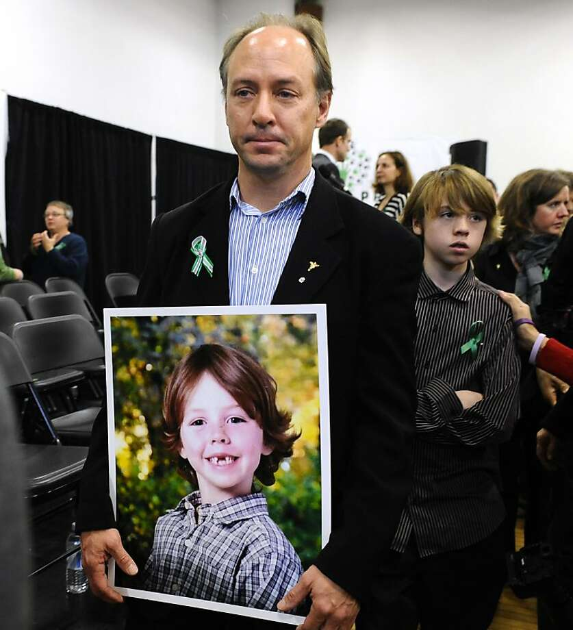 John Barden, father of Sandy Hook Elementary School shooting victim Daniel Barden holds a photograph of his son as he leaves a news conference at Edmond Town Hall in Newtown, Conn., Monday, Jan. 14, 2013. One month after the mass school shooting at Sandy Hook Elementary School, the parents joined a grassroots initiative called Sandy Hook Promise to support solutions for a safer community. (AP Photo/Jessica Hill) Photo: Jessica Hill, Associated Press