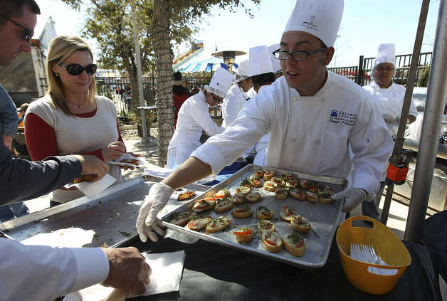 Culinary student Diego Peinado serves up an appetizer of crostini to be paired with a wine at the H-E-B Wine Garden. Photo: Kin Man Hui / San Antonio Express-News
