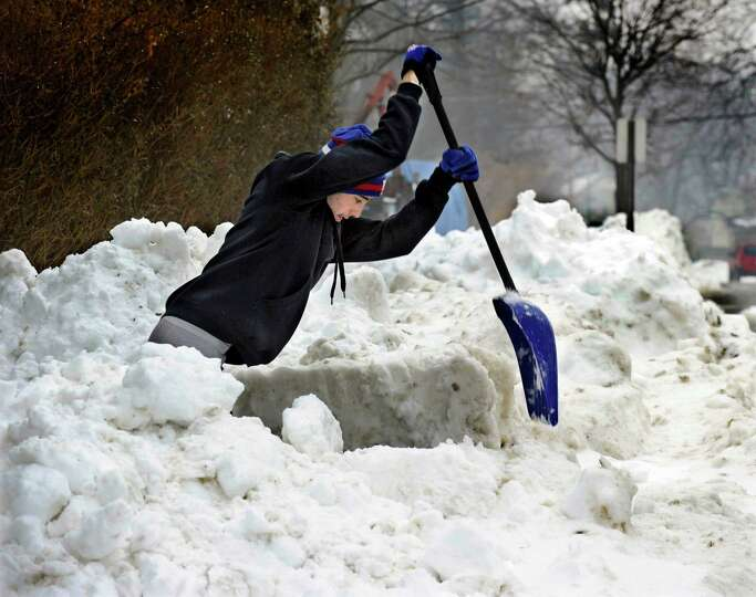 Anthony Batista, 16, comes down hard with a shovel to loosen the snow he is clearing from a sidewalk