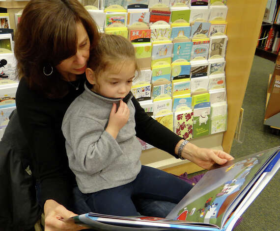 "Weston resident Joan Schnider and granddaughter Juliet Jannes, 4, read Peter Yarrow's new book, ""I'm in Love with a Big Blue Frog,"" at Barnes & Noble book store, where the singer promoted the book Wednesday.  WESTPORT NEWS, CT 2/20/13 Photo: Mike Lauterborn / Westport News contributed"