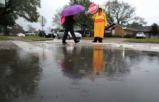 HISD crossing guard Essie McKinney holds traffic to allow students from Lewis Elementary School to reach the premises safely as light rain falls in the area on Thursday, Feb. 21, 2013, in Houston. Photo: Mayra Beltran, Houston Chronicle / © 2013 Houston Chronicle
