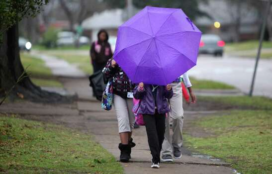 Lewis Elementary School students play in light rain as they walk to school on Thursday, Feb. 21, 2013, in Houston. Photo: Mayra Beltran, Houston Chronicle / © 2013 Houston Chronicle