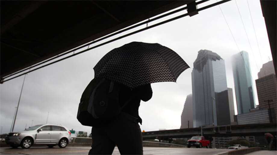 A pedestrian walks into downtown while it drizzles on Thursday, February 21, 2013. Photo: Mayra Beltran / Houston Chronicle