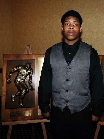 2012 defensive finalist for the Coach Willie Ray Smith, Sr. Award, Joe Lynch, from West Orange - Stark High School stands next to the award at the MCM Elegante' on Wednesday, February 20, 2013.  Photo taken: Randy Edwards/The Enterprise Photo: Randy Edwards