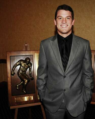 2012 defensive finalist for the Coach Willie Ray Smith, Sr. Award, Korbin Stampley, from Nederland High School stands next to the award at the MCM Elegante' on Wednesday, February 20, 2013.  Photo taken: Randy Edwards/The Enterprise Photo: Randy Edwards