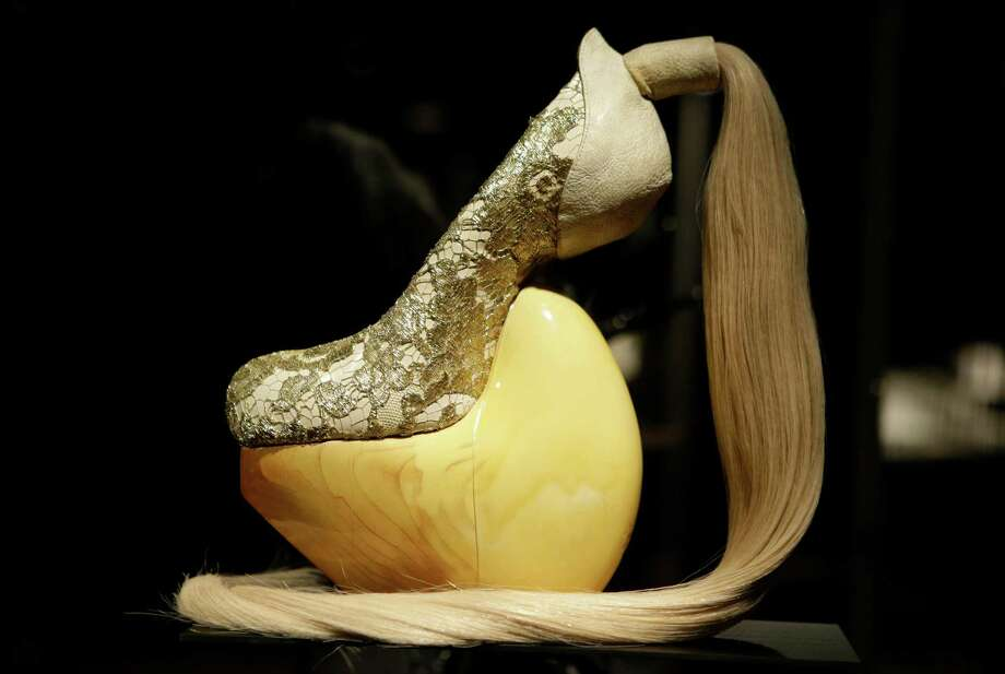 "This Feb. 11, 2013 photo shows a shoe, designed by Masaya Kushino, and made with lacquered Japanese cypress wood, human hair, and lace, displayed at the ""Shoe Obsession"" exhibit at The Museum at the Fashion Institute of Technology Museum in New York. The exhibition, showing off 153 specimens, runs through April 13. Photo: Kathy Willens, AP / AP"