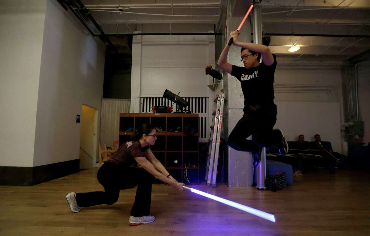 Student Aaron Cheng jumps over a light saber swung by fellow student Starshine Medeiros during a Golden Gate Knights class in San Francisco, Sunday, Feb. 10, 2013. A group of San Francisco Star Wars fans who want to travel to a galaxy not that far away have created a combat choreography class for Jedis-in-training with their weapon of choice: the light saber.