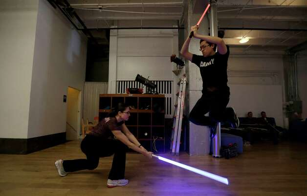 Student Aaron Cheng jumps over a light saber swung by fellow student Starshine Medeiros during a Golden Gate Knights class in San Francisco, Sunday, Feb. 10, 2013. A group of San Francisco Star Wars fans who want to travel to a galaxy not that far away have created a combat choreography class for Jedis-in-training with their weapon of choice: the light saber. Photo: Jeff Chiu, AP / AP