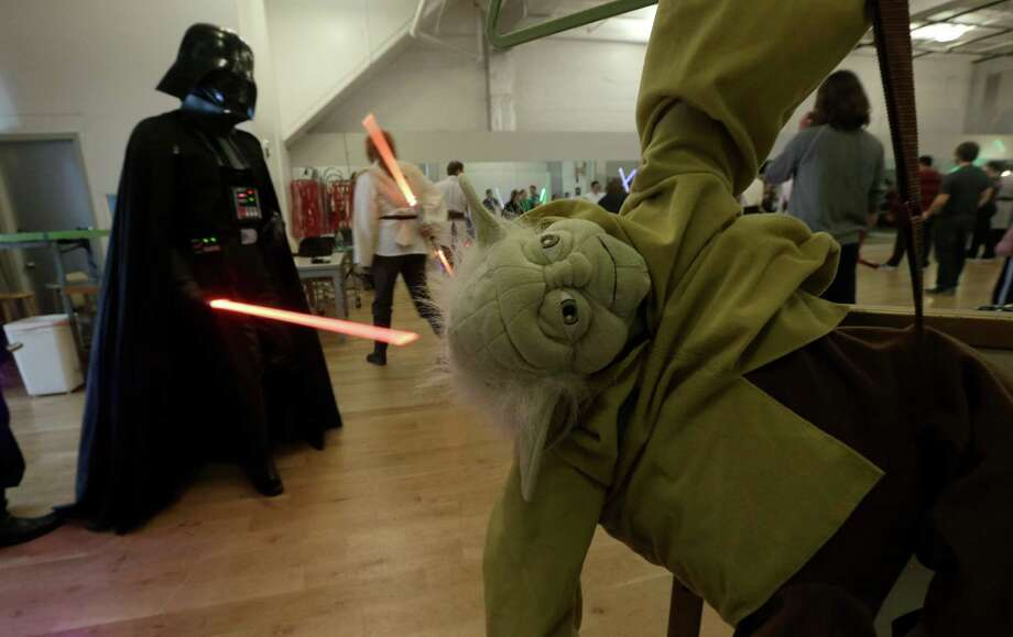Gary Ripper, dressed as Darth Vader, walks past a Yoda doll during Golden Gate Knights class in San Francisco, Sunday, Feb. 10, 2013. A group of San Francisco Star Wars fans who want to travel to a galaxy not that far away have created a combat choreography class for Jedis-in-training with their weapon of choice: the light saber. Photo: Jeff Chiu, AP / AP