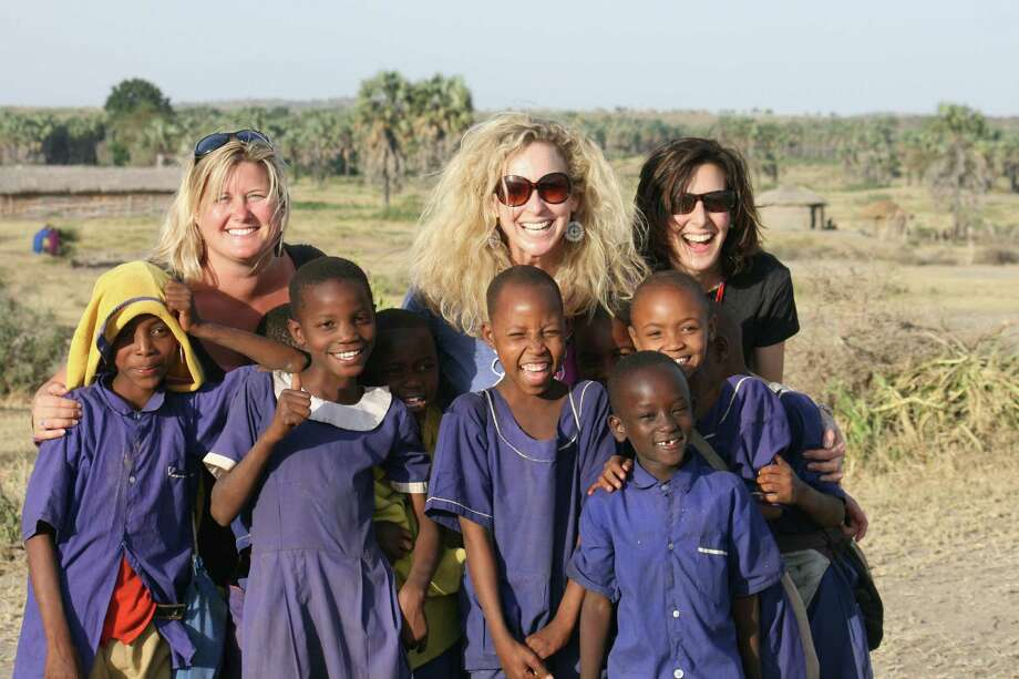 Left, Ashley Holmer, founder and director of the Red Sweater Project, which will benefit from the Girl Rising event in March; center, Ann Wells, founder and director of Unite the World with Africa; and right, Kim Merriman, managing director of Unite, pose with children in Tanzania during a visit in 2012. Photo: Contributed Photo