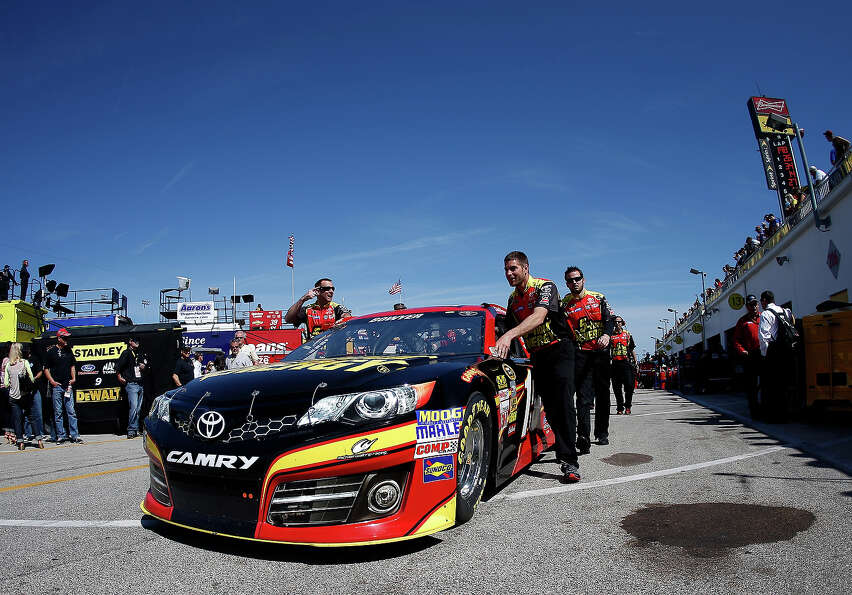 Crew members push the #15 5-hour ENERGY Toyota, driven by Clint Bowyer, throught the garage area dur