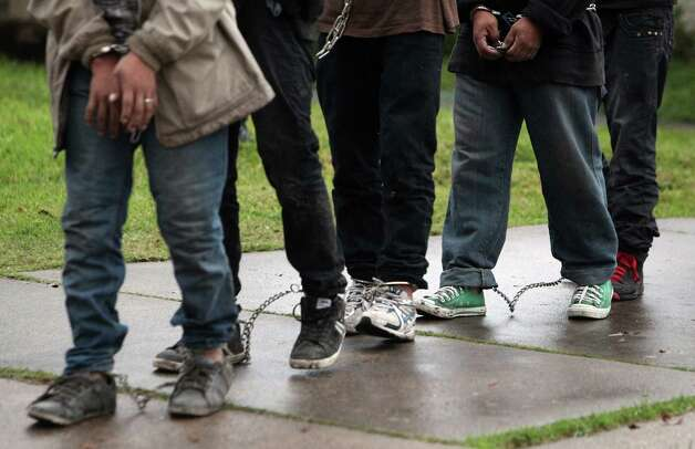 In shackles and handcuffs, approximately 30 undocumented immigrants are transported to an ICE detention center after raiding a home along the 8500 block of Glenaire St. on Thursday, Feb. 21, 2013, in Houston. Photo: Mayra Beltran, Houston Chronicle / © 2013 Houston Chronicle